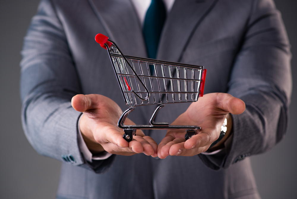 Businessman holding shopping cart in business concept